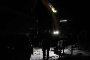 dark picture of excavator and man